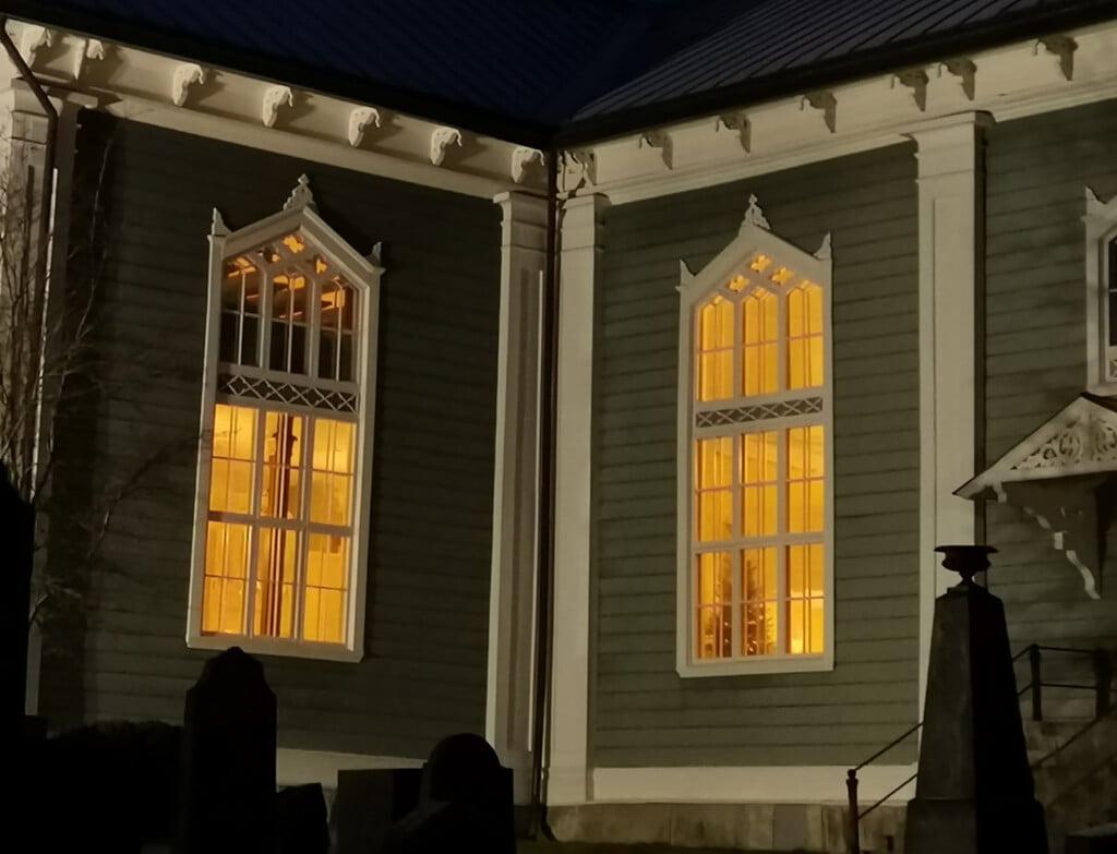 Urjalan kirkon ikkunoista loistaa valoa kirkkomaalle