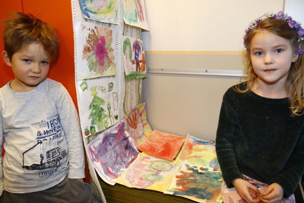 Kuvassa on kaksi pientä lasta ja värikkäitä vesivärimaalauksia.