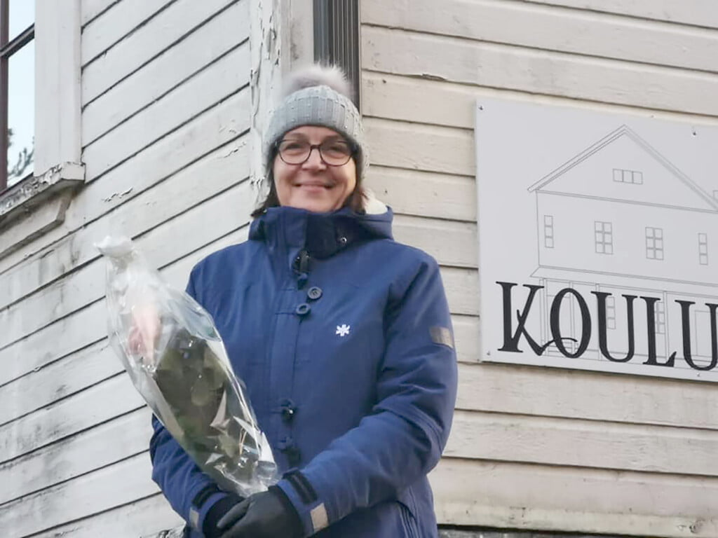 Eila Jouttunpää seisoo Koulumaan edessä ruusu kädessään.